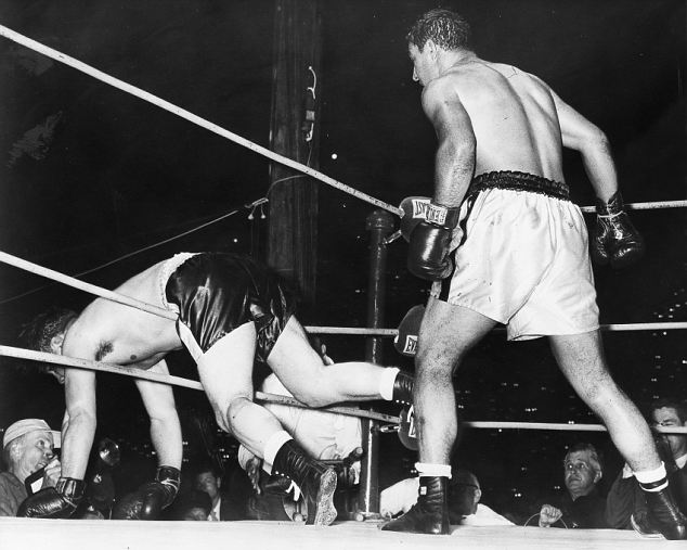 A long right to the chin from Marciano in round eight leaves Cockell draped through the ropes. The champion holds off on this occasion, waiting to see if his opponent will recover. At other times during the fight Marciano wasn't quite so restrained; some observers went so far as to castigate him for flagrant breaches of the rules. He was certainly guilty of more than one low blow, and of hitting Cockell when he was going down. Marciano also butted, elbowed and thumbed his man, all with impunity. 16 May 1955