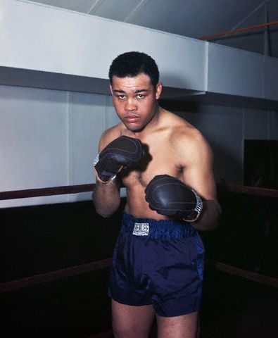 "USA --- Boxing great Joe Louis, the ""Brown Bomber"", stands in a gymnasium boxing ring as if ready for a match. --- Image by © Bettmann/CORBIS"