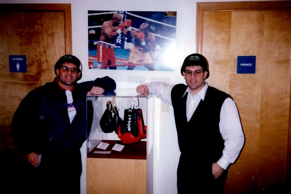 "The Boxing Twins wearing Leonard-Hearns II promotional ""WAR"" army helmits standing next to Alex's photo of the Foreman-Moorer bout displayed in the Boxing Hall of Fame"