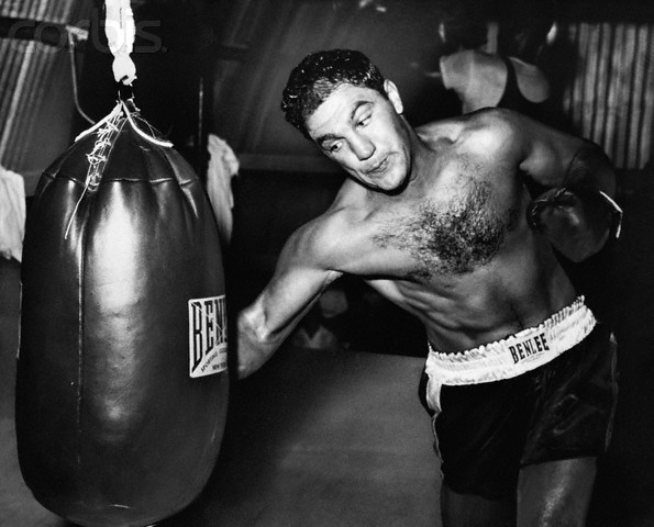 18 Aug 1955, Grossinger, New York, USA --- 8/18/1955- Grossinger, NY: Solid defender. World heavyweight champion Rocky Marciano gets in some licks with the big bag while training here for his forthcoming bout with Archie Moore. Marciano will defend his title against the light heavyweight champion September 20th at Yankee Stadium. --- Image by © Bettmann/CORBIS