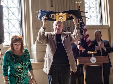 Chuck Wepner holds up his belt made by SARTNONK - commissioned by Bayonne, NJ