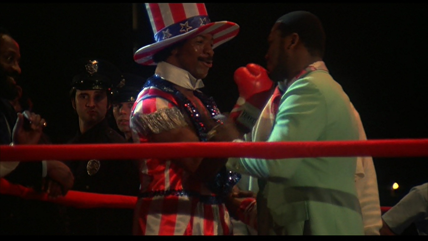 Apollo Creed (Carl Weathers) and Joe Frazier in Rocky film with punch.