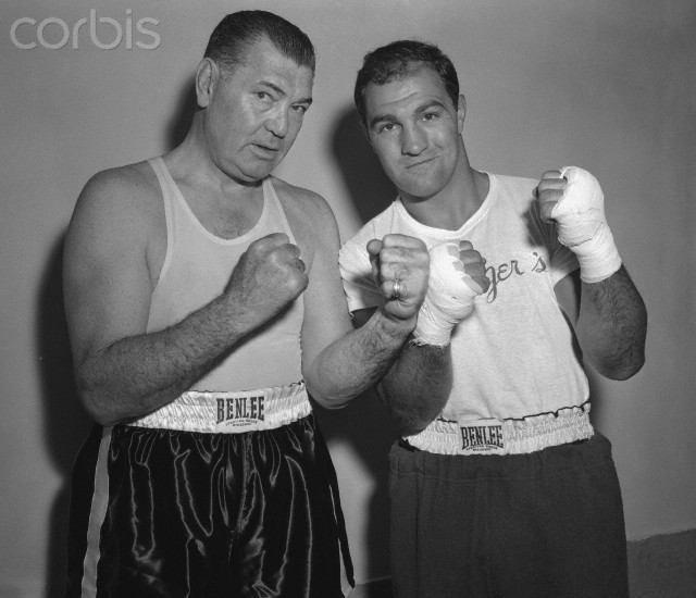 02 Sep 1954, Grossinger, New York State, USA --- Original caption: Former heavyweight champ Jack Dempsey (left) and present champ Rocky Marciano hold up their fists, just for size. Jack visited Rocky's training camp here to see the champ work out for his return match and title defense with Ezzard Charles. He refused to make any predictions on the outcome of the Sept. 15th bout before seeing Charles work out. --- Image by © Bettmann/CORBIS