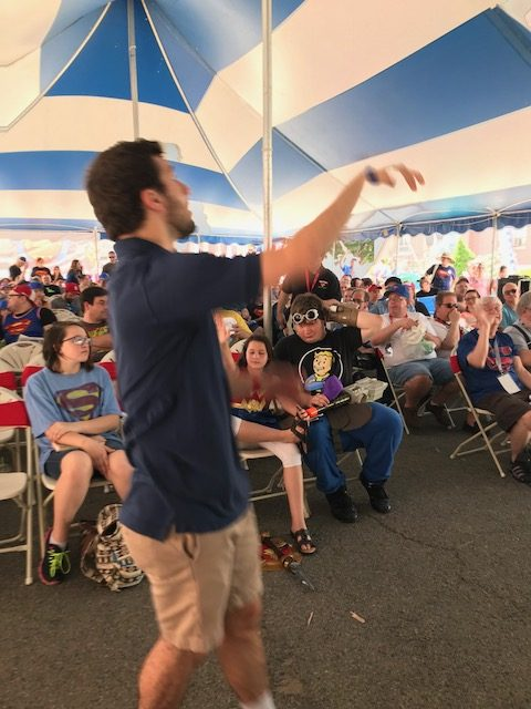 Alexander Rinaldi throwing prizes out to audience during Superman Jeopardy game