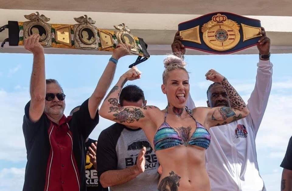 Reigning Police Gazette World Diamond Belt Holder Bec Rawlings at Weigh-ins in CanCun, Mexico. Belfast's Scott Burt holds the World's Oldest Active belt she successfully defends up for display behind her.
