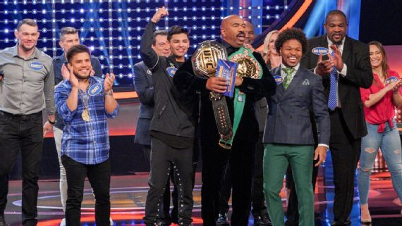Host Steve Harvey with the contestants and the belts.