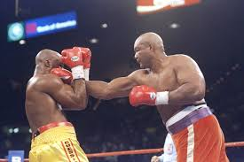 George Foreman (R) clocks heavyweight champion Michael Moorer (L) in their 1994 bout where Foreman captured the heavyweight title.